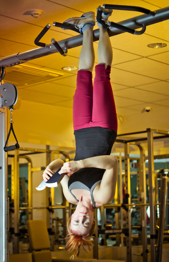 Athletic young woman hanging upside down and reading book